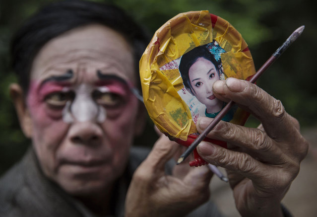 Sichuan Opera performer Yi Lezhing, 65 years, of the Jinyuan Opera Company puts on make -up before the group's performance for villagers at the Dongyue Temple on May 2, 2016 in Cangshan, Sichuan province, China. (Photo by Kevin Frayer/Getty Images)