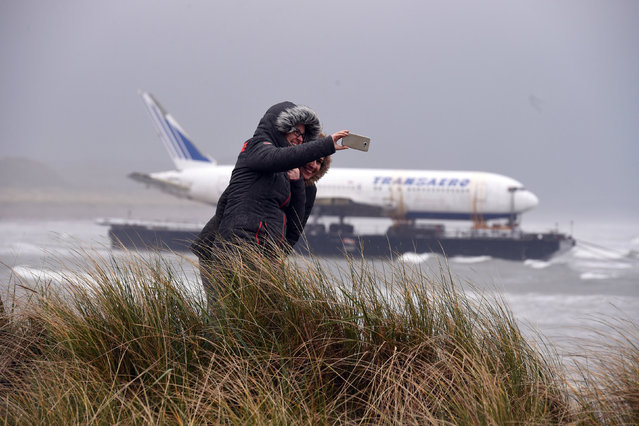 Two women take a picture of a Boeing 767 airplane as it arrived onto Enniscrone beach after it was tugged from Shannon airport out to sea around the west coast of Ireland, May 7, 2016. (Photo by Clodagh Kilcoyne/Reuters)