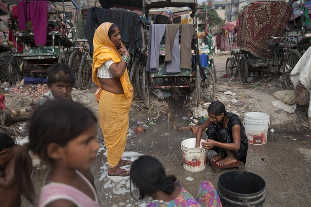 An Indian girl bathes beside a woman brushing her teeth at a shanty area in New Delhi, India, Tuesday, June 30, 2015. There is no direct supply of potable water at homes in most of the poor neighborhoods in the country and people have to depend on regulated supply of water from public taps erected on roadsides, with a single tap catering to hundreds of households. (Photo by Tsering Topgyal/AP Photo)