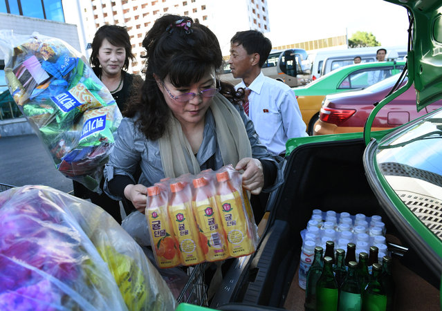 Patrons of the Kwangbok (which means revolution) department / grocery store load plastic flowers and food into their trunk in  Pyongyang, North Korea on May 4, 2016. The items will likely be used in the upcoming Workers' Party festivities celebrating the seventh congress in their nation's history. The last such event was held in 1980. (Photo by Linda Davidson/The Washington Post)