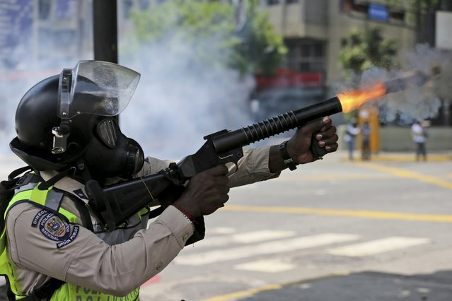 A Venezuelan Bolivarian National Police officer fires tear gas towards demonstrators during a protest in Caracas, Venezuela, Monday, April 10, 2017. (Photo by Fernando Llano/AP Photo)