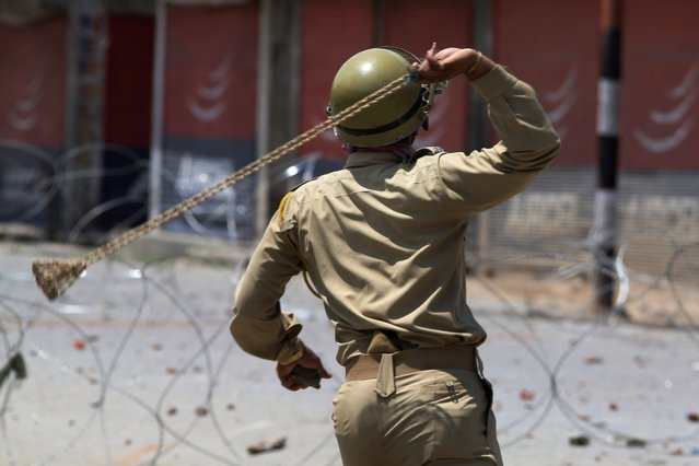 An Indian policeman uses a sling to hurl stones at Kashmiri protesters during a protest following calls by rebels and separatist politicians to boycott the Indian parliamentary elections in Baramulla, some 55 kilometers north of Srinagar, India, Wednesday, May 7, 2014. Violence flared in Indian-controlled Kashmir on Wednesday as millions of Indians voted in the penultimate day of national elections. (Photo by Dar Yasin/AP Photo)