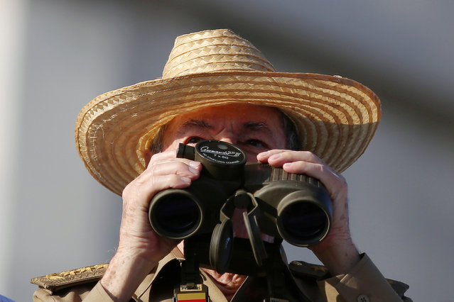 Cuba's President Raul Castro looks through a binocular as he watches a May Day rally in Havana, Cuba on May 1, 2017. (Photo by Alexandre Meneghini/Reuters)