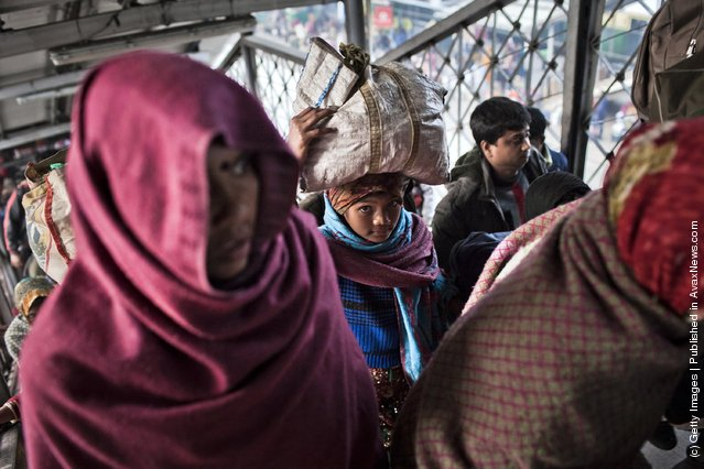 People carry their belongings after alighting from a train at the Nizamuddin Railway Station in New Delhi, India
