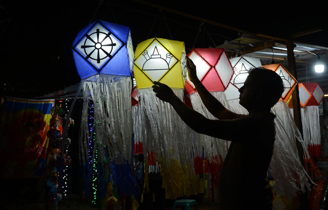 A Sri Lankan street vendor hangs lanterns for sale ahead of the Vesak Festival in Colombo on May 4, 2017. Sri Lankan Buddhists are preparing to celebrate Vesak, which commemorates the birth of Buddha, his attaining enlightenment and his passing away on the full moon day of May which falls on May 10 this year. (Photo by Lakruwan Wanniarachchi/AFP Photo)