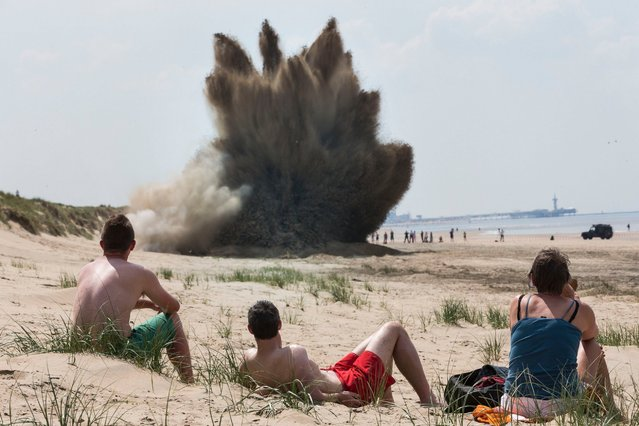 Beachgoers watch the detonation of a 500 pound British bomb on the beach on May 19, 2014 in Wassenaar, Netherlands. The bomb was dropped by the British allied forces during the second world war over nearby Leiden where it was found on a building site. (Photo by Michel Porro/Getty Images)