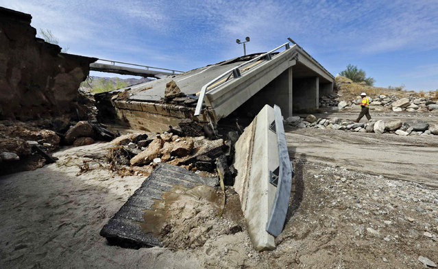 A worker walks near a washed-out bridge near the town of Desert Center, along Interstate 10 in Southern California, on Monday, July 20, 2015. (Photo by Nick Ut/AP Photo)
