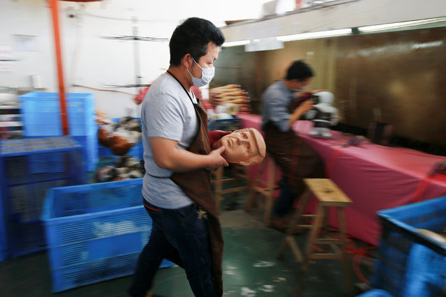 A worker carries a freshly made mask of U.S. Republican presidential candidate Donald Trump at Jinhua Partytime Latex Art and Crafts Factory in Jinhua, Zhejiang Province, China, May 25, 2016. (Photo by Aly Song/Reuters)