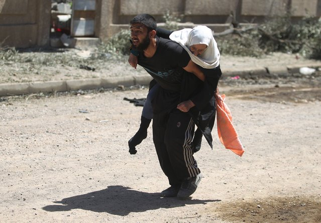 Displaced Iraqis from Mosul's western Rabie neighbourhood flee their homes as security forces advance into the area during the ongoing offensive against Islamic State (IS) group fighters on May 17, 2017. (Photo by Ahmad Al-Rubaye/AFP Photo)