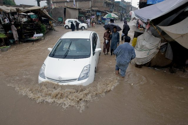A car drives through a flooded street after heavy rains in a suburb of Peshawar, Pakistan, Thursday, July 23, 2015. (Photo by Mohammad Sajjad/AP Photo)