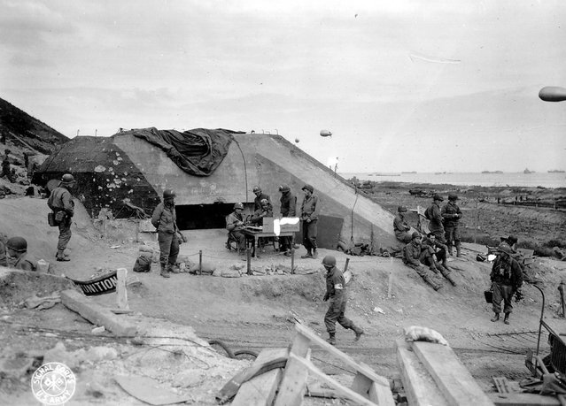 U.S. Army troops congregate around a signal post used by engineers on the site of a captured German bunker overlooking Omaha Beach after the D-Day landings near Saint Laurent sur Mer, June 7, 1944. REUTERS/US National Archives