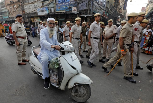 A Muslim man rides a scooter as police officers conduct a flag march in a street outside Jama Masjid, before Supreme Court's verdict on a disputed religious site claimed by both majority Hindus and Muslim in Ayodhya, in the old quarters of Delhi, India, November 9, 2019. (Photo by Adnan Abidi/Reuters)