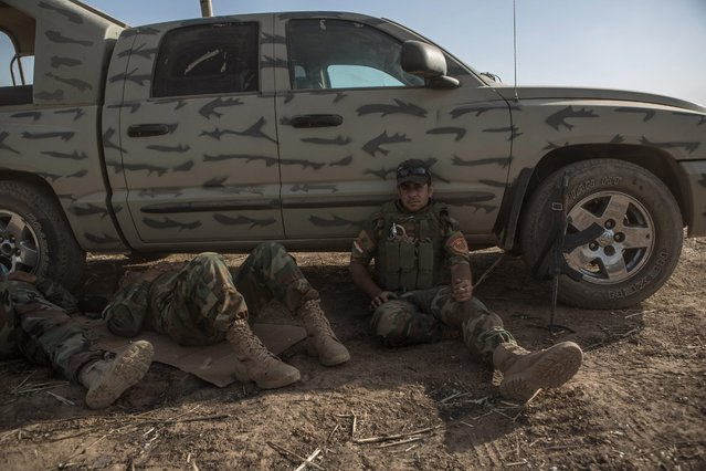 A photograph made available on 30 May 2016 shows Peshmerga fighters resting on the outskirts of Mufti village after it was recaptured from Islamic State (IS) fighters, Kurdistan region, north Iraq, 29 May 2016. Reports state the Kurdish Regional Government launched an offensive to take back villages that fell to the Islamic State (IS) in 2014, as part of the ongoing efforts to clear a path to retake Mosul, Iraq's second largest city. (Photo by Andrea Dicenzo/EPA)