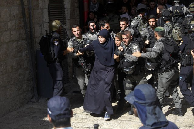 Israeli border police officers scuffle with Palestinian women in the Old City of Jerusalem on Sunday, July 26, 2015. Israeli police said they entered the al-Aqsa Mosque, a holy Jerusalem site, to prevent Arab youths from attacking visiting Jews marking a biblical holiday. (Photo by Mahmoud Illean/AP Photo)