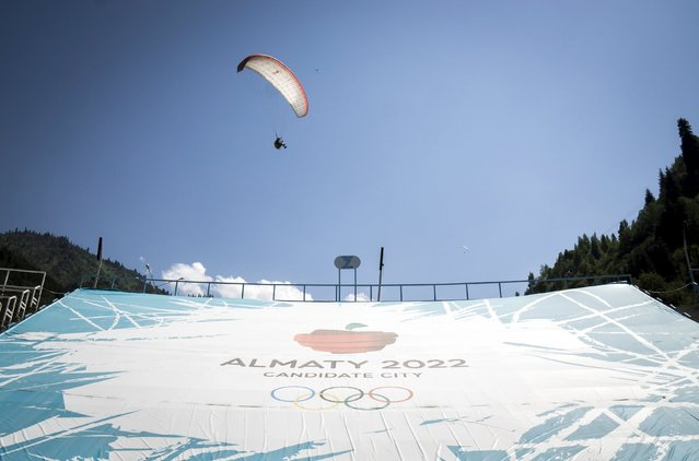 A paraglider flies over a banner promoting Almaty candidate city for 2022 Winter Olympic Games at the Medeu skating oval in Almaty, Kazakhstan, July 26, 2015. Kazakhstan is aspiring to host the 2022 Winter Olympics but many in the Central Asian nation view the bid as yet another vanity project of long-ruling President Nursultan Nazarbayev. Almaty, the financial capital, will go head-to-head with the Chinese metropolis Beijing on Friday when the International Olympic Committee elects the winner at its session in Malaysia. (Photo by Shamil Zhumatov/Reuters)
