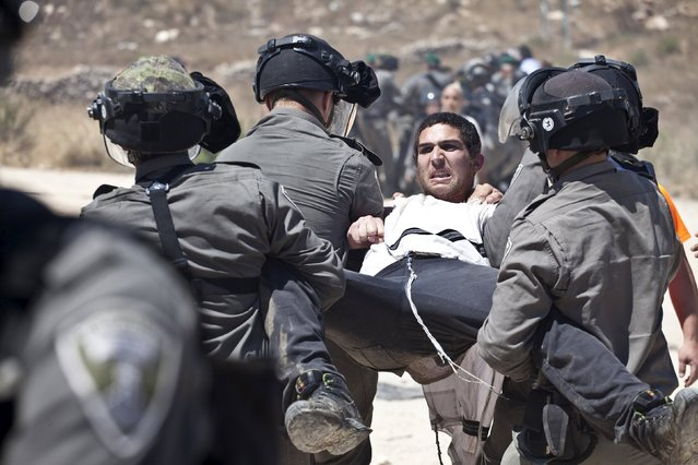 Israeli paramilitary police detain a Jewish settler protesting the demolition of two partially-built dwellings in the West Bank Jewish settlement of Beit El near Ramallah July 29, 2015. Israel gave final approval on Wednesday for plans to build 300 new homes in the Jewish settlement in the occupied West Bank, announcing the move as it carried out a court demolition order against the two vacant apartment blocs at the site. (Photo by Emil Salman/Reuters)