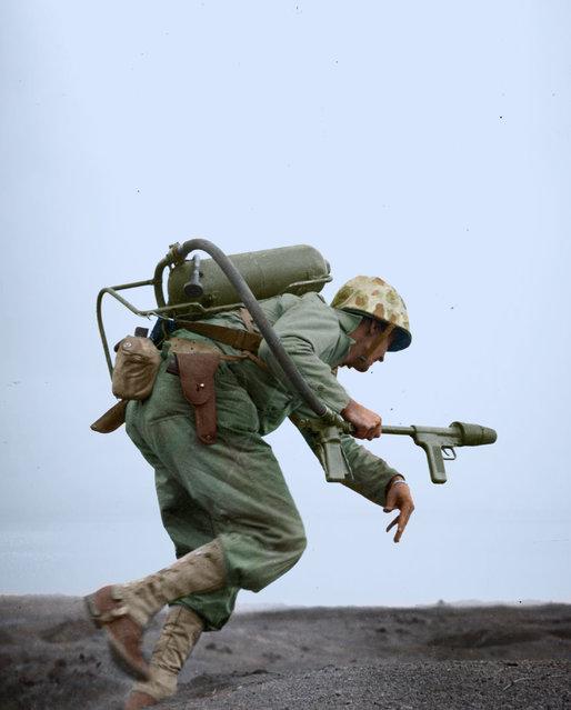 A Marine flamethrower operator moves forward to assault a Japanese pillbox on Motoyama Airfield, ca. Feb-Mar 1945. (Photo by Jared Enos/Mediadrumworld.com)