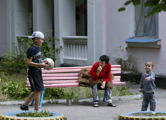 A woman sits on a bench as boys play in the compound of a health and rest centre which serves as a temporary accommodation for refugees from eastern regions of the country in the town of Korostyshiv, Zhytomyr region, Ukraine, July 30, 2015. (Photo by Valentyn Ogirenko/Reuters)
