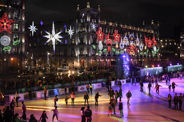 People skate on an acrilic rink placed in the Zocalo square with the City Hall showing Christmas decorations in the background in Mexico City on December 17, 2019. (Photo by Pedro Pardo/AFP Photo)