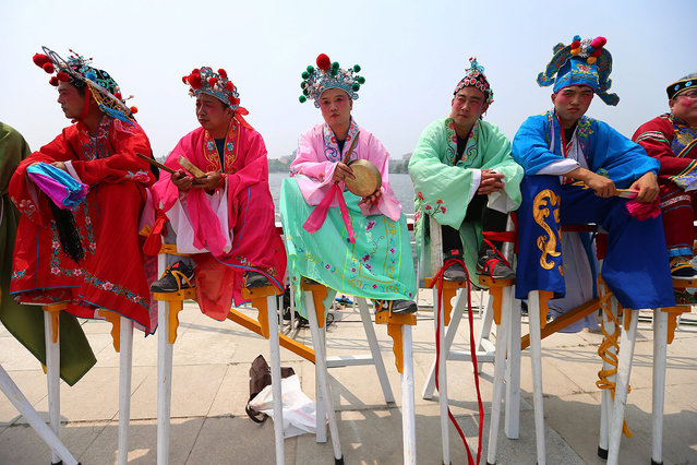 Entertainers prepare to perform a Chinese traditional dance on stilts during the Chinese traditional Dragon Boat Festival at a park in Beijing, China, 09 June 2016. The event, also named Duanwu Festival, falls on the fifth day of the fifth month of the Chinese lunar calendar in honor of Qu Yuan, an ancient Chinese poet and statesman. (Photo by Wu Hong/EPA)