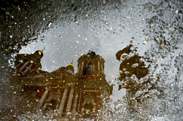 A man is reflected in a puddle as he walks past Orthodox St. Clement's Church in downtown Moscow on December 4, 2019. (Photo by Kirill Kudryavtsev/AFP Photo)