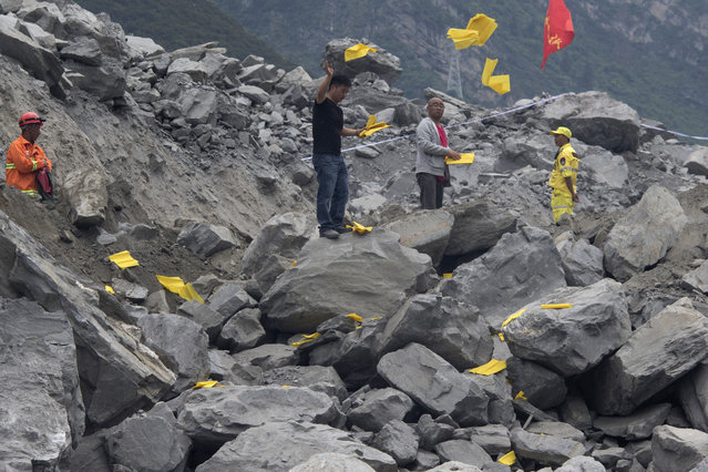 Relatives toss paper offerings to appease the dead at the site of a landslide in Xinmo village in Maoxian County in southwestern China's Sichuan Province, Sunday, June 25, 2017. (Photo by Ng Han Guan/AP Photo)