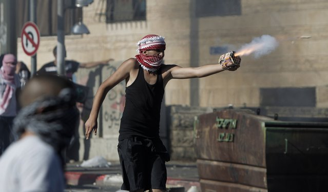 A Palestinian protestor directs fireworks toward Israeli police during clashes in Shuafat neighborhood in Israeli-annexed Arab East Jerusalem, on July 2, 2014, after a Palestinian teenager was kidnapped and killed in an apparent act of revenge for the murder by militants of three Israeli youths. (Photo by Ahmad Gharabli/AFP Photo)