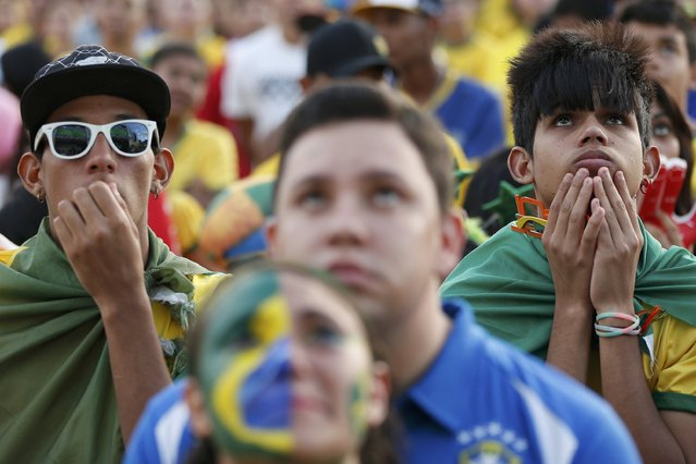 Fans of Brazil react while watching a broadcast of the 2014 World Cup semi-final against Germany at the Fan Fest in Brasilia, July 8, 2014. (Photo by Ueslei Marcelino/Reuters)
