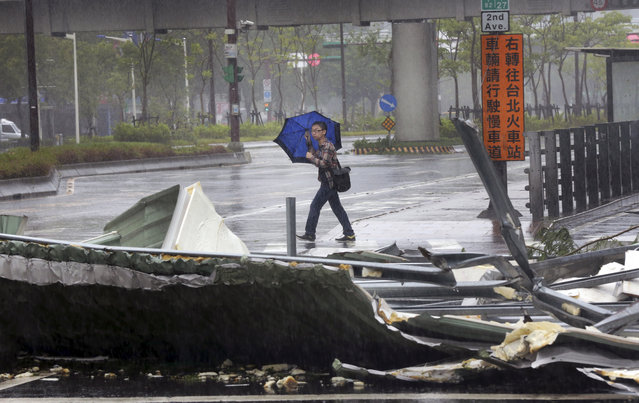 A man carrying an umbrella passes a mangled rooftop brought down by strong winds from Typhoon Soudelor in Taipei, Taiwan, Saturday, August 8, 2015. (Photo by Wally Santana/AP Photo)