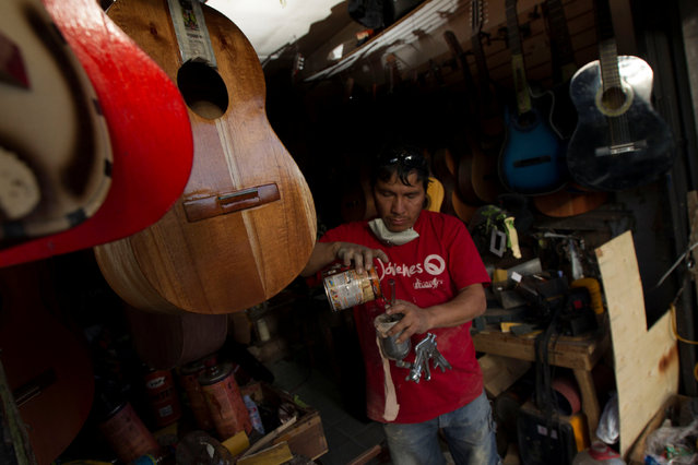 Ecuadorian luthier Ivan Ibujes prepares paint for a guitar after repairing it at his shop in Quito, June 17, 2016. (Photo by Guillermo Granja/Reuters)
