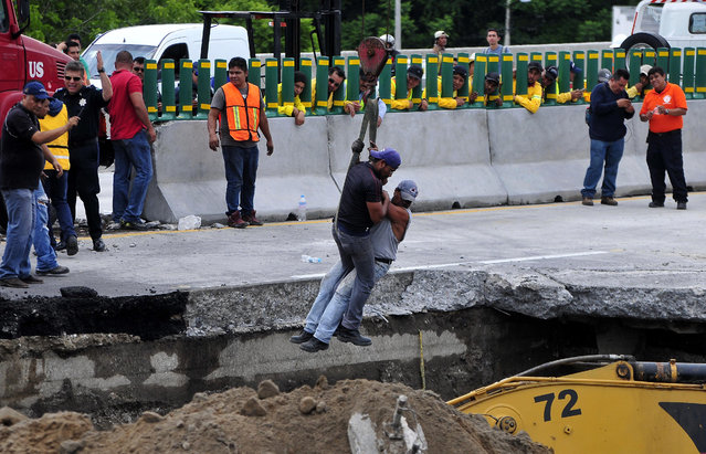 Workers are lowered by a crane as they work to rescue a vehicle that drove into a sinkhole that opened up on a highway in Cuernavaca, Mexico, Wednesday, July 12, 2017. A father and son were killed when the deep sinkhole swallowed their car on Wednesday morning. Civil protection rescuers reached the rubble-covered Volkswagen Jetta lying on its roof at the bottom of the hole in the afternoon, after working for more than eight hours on the closed section of road. (Photo by Tony Rivera/AP Photo)