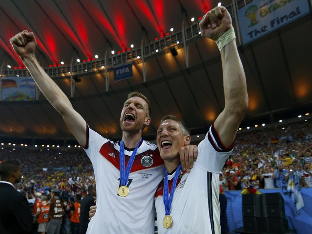 Germany's Per Mertesacker celebrates with Bastian Schweinsteiger after winning their 2014 World Cup final against Argentina at the Maracana stadium in Rio de Janeiro July 13, 2014. (Photo by Eddie Keogh/Reuters)