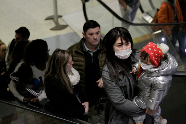 Travellers wearing masks arrive on a direct flight from China, after a spokesman from the U.S. Centers for Disease Control and Prevention (CDC) said a traveller from China had been the first person in the United States to be diagnosed with the Wuhan coronavirus, at Seattle-Tacoma International Airport in SeaTac, Washington, U.S. January 23, 2020. (Photo by David Ryder/Reuters)