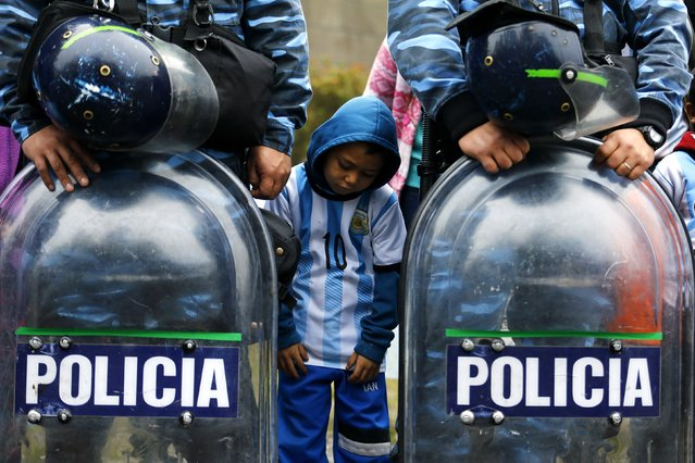 An Argentine fan stands between policemen as they gather to welcome their team outside the Argentine Football Association (AFA) after Argentina lost to Germany in their 2014 World Cup final soccer match, in Buenos Aires, July 14, 2014. (Photo by Ivan Alvarado/Reuters)