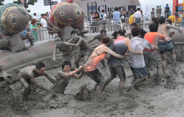 Participants play in a mud pool during the Boryeong Mud Festival at Daecheon Beach in Boryeong, South Korea, Friday, July 18, 2014. The 17th annual mud festival features mud wrestling and mud sliding. (Photo by Ahn Young-joon/AP Photo)