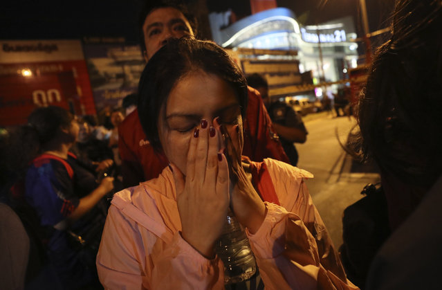 A woman who was able to get out of Terminal 21 Korat mall gestures with her hands on her face in Nakhon Ratchasima, Thailand on Sunday, February 9, 2020. (Photo by Sakchai Lalitkanjanakul/AP Photo)