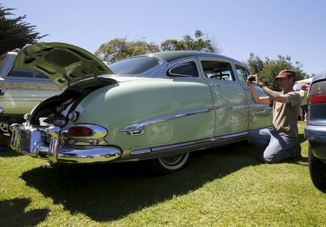 """A man takes a photograph of a 1953 Hudson during the """"Worst of Show"""" at the Concours d'Lemon, part of the Pebble Beach Concours d'Elegance in Seaside, California, August 15, 2015. (Photo by Robert Galbraith/Reuters)"""