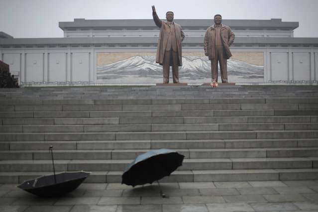 Umbrellas are left at the bottom of the stairs as people pay their respects and lay flowers at the foot of giant bronze statues of their late leaders Kim Il Sung and Kim Jong Il at Munsu Hill on Thursday, July 27, 2017, in Pyongyang, North Korea as part of celebrations for the 64th anniversary of the armistice that ended the Korean War. (Photo by Wong Maye-E/AP Photo)