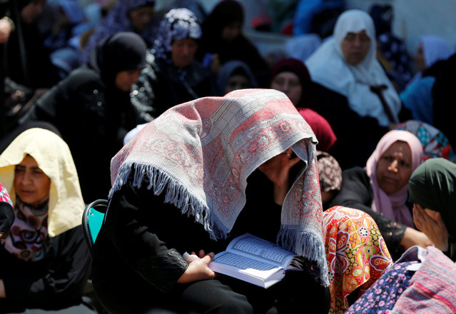 A Palestinian woman reads the Koran on the last Friday of the holy fasting month of Ramadan on the compound known to Muslims as Noble Sanctuary and to Jews as Temple Mount in Jerusalem's Old City July 1, 2016. (Photo by Ammar Awad/Reuters)