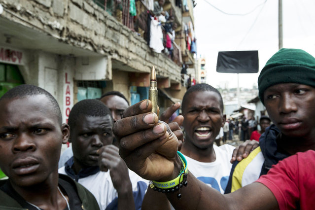 Kenyans show a bullet to photographers, which they claim was fired by police attempting to calm an unruly mob in Mathare slums, as violent protest ensue following the final votes from Kenya's general election being counted in Nairobi, Kenya, 09 August 2017. Provisional results of the Presidential poll shows the incumbent Uhuru Kenyatta leading opposition leader Raila Odinga, who rejected them saying that the official tally doesn't match their own counts. The police are beefing up security on Nairobi streets as the fear of post-election violence looms. (Photo by Kabir Dhanji/EPA)