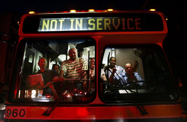 "Commuters stand in a bus displaying ""Not in Service"" during a massive blackout August 15, 2003 in New York City. Power is slowly returning to certain parts of the city. (Photo by Mario Tama/Getty Images)"