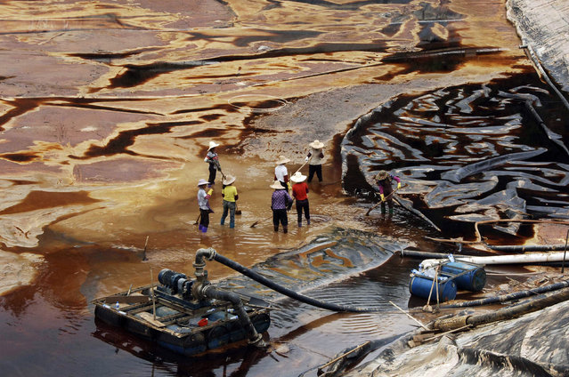Labourers work to drain sewage water from a leaked sewage tank at a copper mine in Shanghang, Fujian province, July 13, 2010. The sewage leak from the copper mine owned by Zijin Mining Group Co, whose shares were suspended from trading in Hong Kong on Monday, has polluted a river and reservoir in Fujian province, Xinhua news agency reported. Xinhua cited environmental authorities as saying the leak from a plant of the Zijinshan Copper Mine had killed or poisoned about 1.89 million kg of fish. (Photo by Reuters/Stringer)