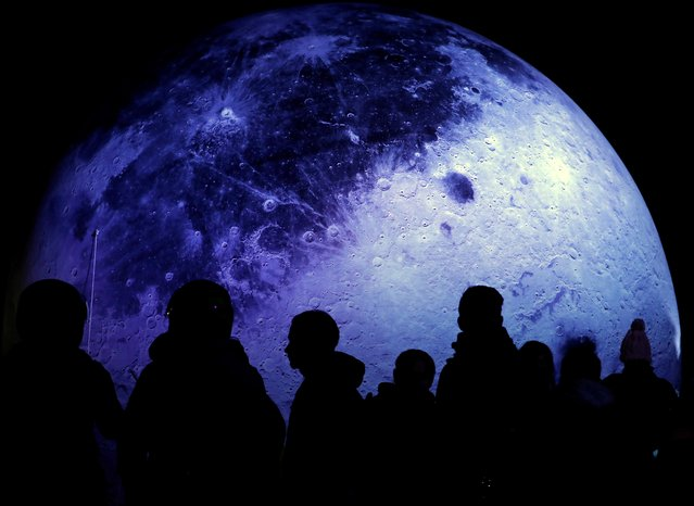 """People are silhouetted as they gather around Milan Rai's art installation """"Lunatic"""", a replica of the Moon, as it is displayed at Patan Durbar Square, a UNESCO world heritage site, in Lalitpur, Nepal on December 22, 2019. According to the artist the idea came as a response to today's individualistic society with the hope for many to find commonality. (Photo by Navesh Chitrakar/Reuters)"""