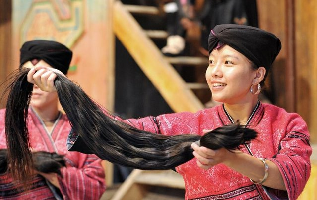 A woman shows the hair cut off from a 18-year-old girl to tourists at the Huangluo Village of the Yao ethnic group in Guilin, south China's Guangxi Zhuang Autonomous Region, July 15, 2012. The Huangluo Village of the Yao ethnic group locates at the Longji Terraces in Heping Town of Longsheng County in Guilin. Women here have the tradition of keeping long hair. They believe that long hair brings good luck and fortune. The average length of hair of 180 women in the village is 1.7 meters. (Photo by Lu Boan/Xinhua)