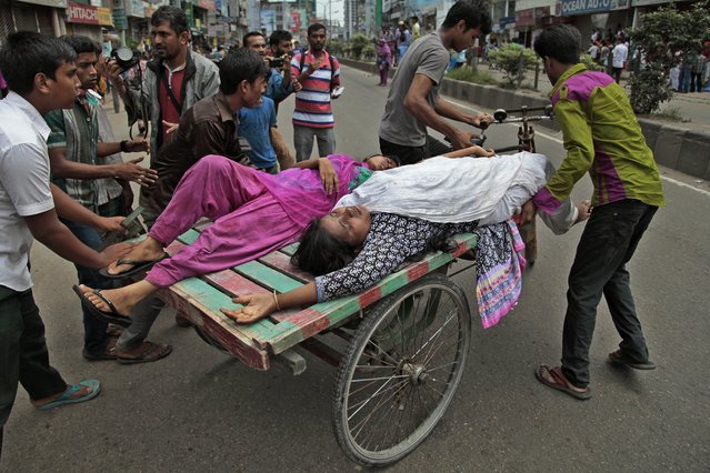Bangladeshi garment workers take away their injured colleagues in a cycle cart during a clash with police in Dhaka, Bangladesh, Thursday, August 7, 2014. Bangladesh police on Thursday entered the premises of a garment factory, fired tear gas and used batons to disperse workers who were on a hunger strike since July 28 demanding payment of their salaries and festival allowances. (Photo by A. M. Ahad/AP Photo)