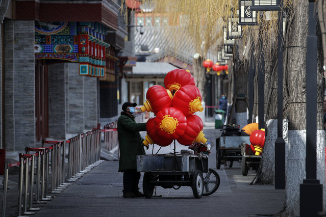 A worker wearing a protective face mask places lanterns on his cart near the closed restaurants along the Houhai Lake, a usually popular tourist spot before the coronavirus outbreak in Beijing, Sunday, March 1, 2020. Amid fears about where the next outbreak of a fast-spreading new virus would appear, infections and deaths continued to rise across the globe Sunday, emptying streets of tourists and workers, shaking economies and rewriting the realities of daily life. (Photo by Andy Wong/AP Photo)