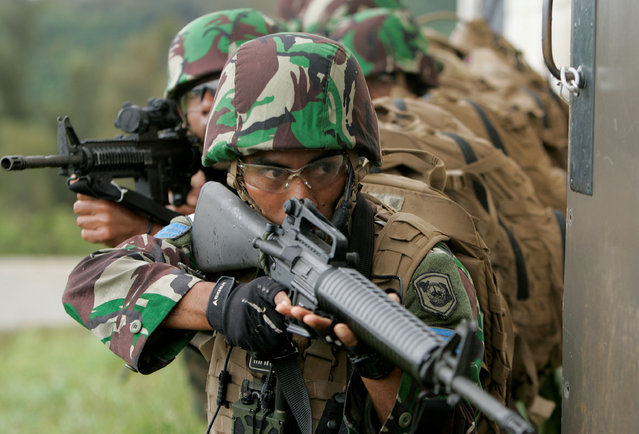 Indonesian Marines prepare to breach a building during a helicopter insertion exercise with US Marines in the Kahuku mountains training area during the multi-national military exercise RIMPAC in Honolulu, Hawaii, July 13, 2016. (Photo by Hugh Gentry/Reuters)
