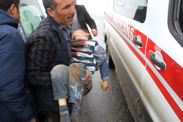 A man carries a wounded boy to an ambulance after an earthquake hit villages in Baskale town in Van province, Turkey, at the border with Iran, Sunday, February 23, 2020. Turkish Interior Minister Suleyman Soylu said numerous people have been killed and several others wounded in Sunday's quake with more people trapped under debris. (Photo by IHA via AP Photo)