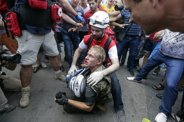 A protester receives medical treatment after clashes with municipal workers and volunteers at Independence Square in Kiev August 9, 2014. (Photo by Konstantin Chernichkin/Reuters)