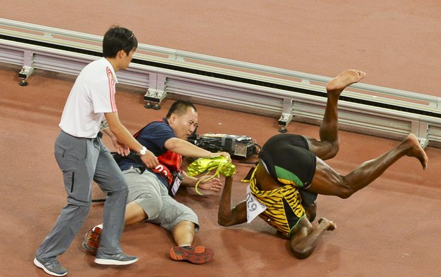 Usain Bolt of Jamaica (R) falls after being knocked over by a cameraman (C) on a Segway as he celebrates after winning the men's 200 metres final during the 15th IAAF World Championships at the National Stadium in Beijing, China, August 27, 2015. (Photo by Reuters/Stringer)